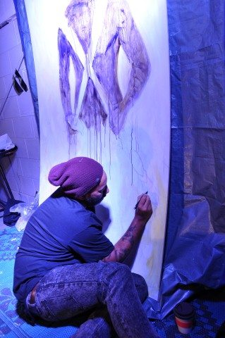 Renowned Kiwi artist, Mike Tupaea painting the taiaha